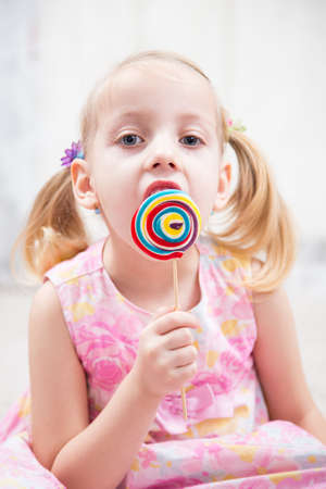 provocative food: little girl eating a tasty sugar candy Stock Photo