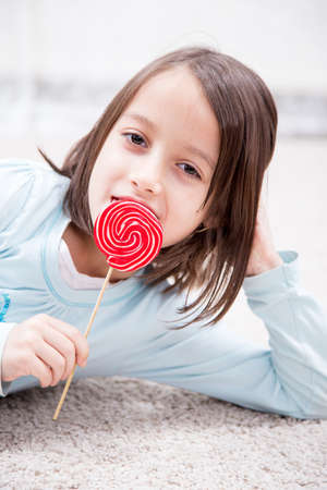 provocative food: happy little girl eating sugar candy