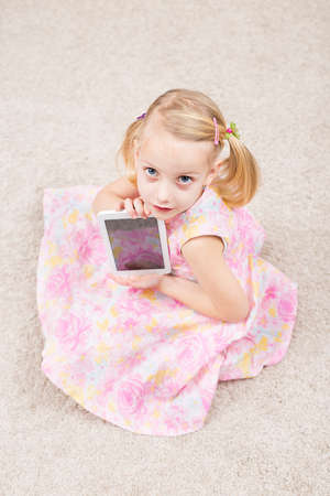 blonde little girl with her tablete Imagens