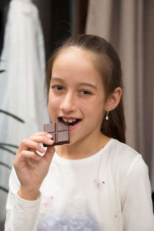 Happy smile girl eating a big chocolate