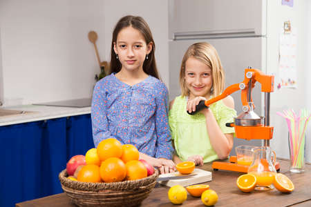 sisters in kitchen, make a juice Imagens