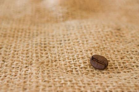 east espresso: Single coffee bean on burlap sack background