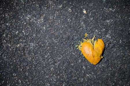smashed: Smashed orange shaped like broken heart on the asphalt