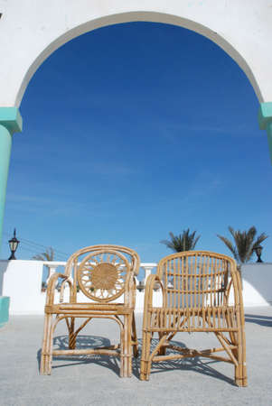 Wattled chairs on a verandah at a sea photo