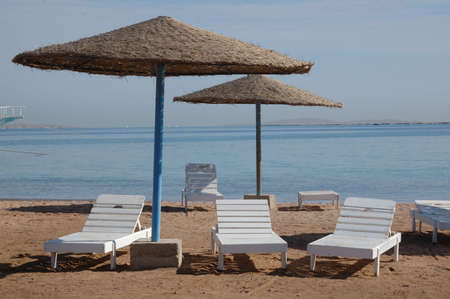 White deck-chairs on the deserted beach Stock Photo - 4331215