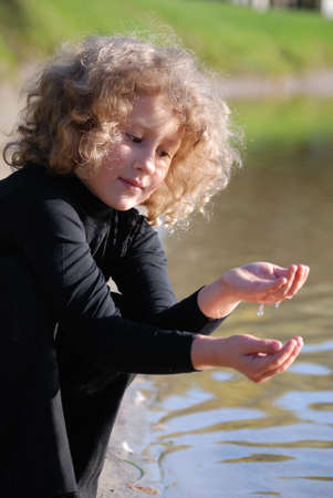 Little girl, playing with water ashore lake Stock Photo - 4339093