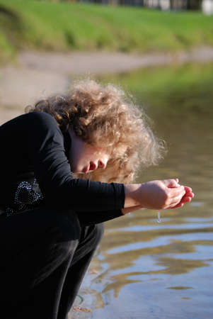 Little girl, playing with water ashore lake Stock Photo - 4339088