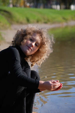 Little girl, playing with water ashore lake Stock Photo - 4339091