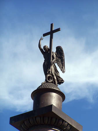 Figure of angel with a cross on a background blue sky photo