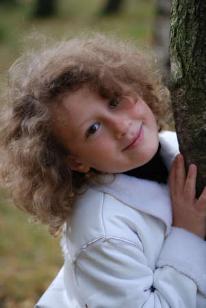 Little girl in a park next to a birch Stock Photo - 4343786