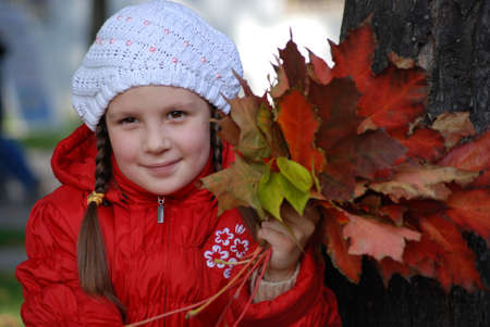 little girl near a tree in an autumn park photo