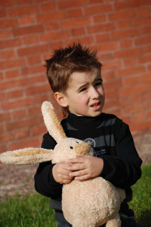 Little boy with a toy hare in hands photo