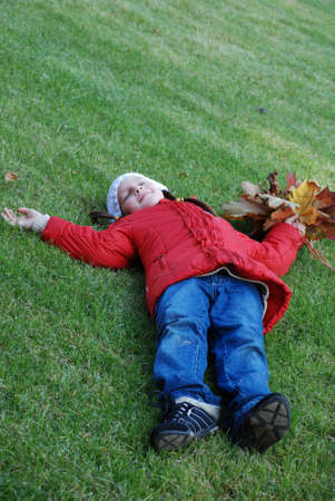 little girl, lying on a green lawn in a park Stock Photo - 4781107
