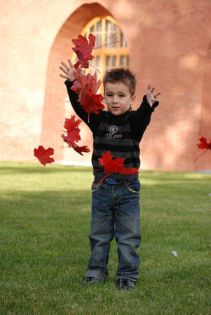 boy, throwing red autumn leaves up photo