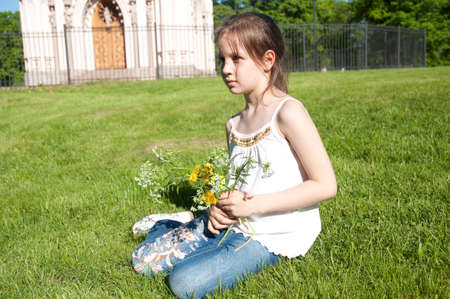 peterhof: Little girl with the bouquet of the field flowers on a background Gothic Choir in Petrodvorce, Saint Petersburg, Russia