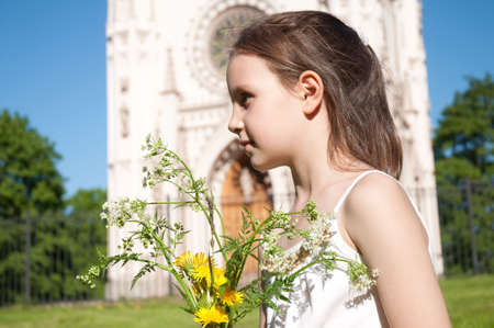 Little girl with the bouquet of the field flowers on a background Gothic Choir in Petrodvorce, Saint Petersburg, Russia photo