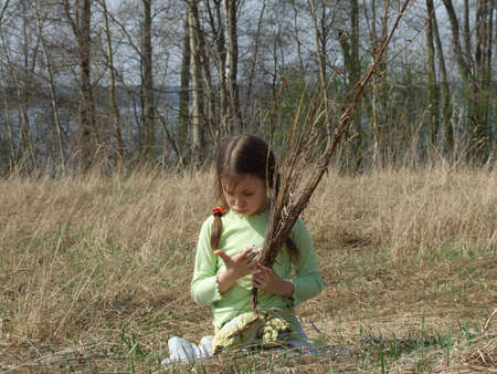little girl in the field with the armful of reed photo