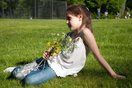 little girl with the bouquet of flowers on a green lawn photo