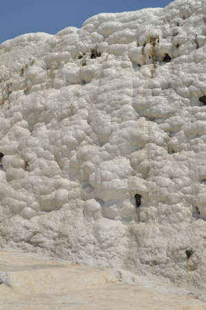 A natural purely white wall of calcium in Pamukkale, a natural site and attraction in south-western Turkey. natural phenomenon of thick white layers of limestone and travertine cascading down the mountain slope resembling a frozen waterfall. photo