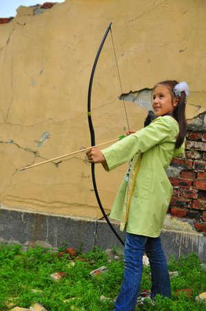 Beauty girl bends bow archer target arrow photo