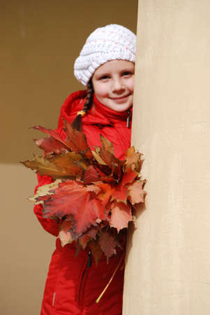 little girl with a bouquet from maple leaves near a column photo