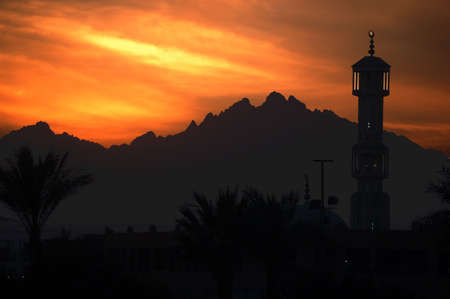 beautiful sunset above mountains and mosque photo