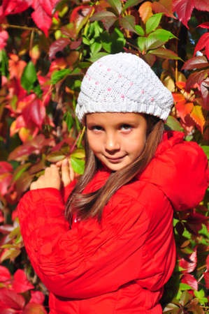 a girl is in an autumn park, next to a fence, twined wild grapes photo