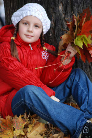 a little girl is in a park, with yellow leaves in hands Stock Photo - 5683190