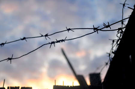 prison system: Barbed wire against the sky Stock Photo