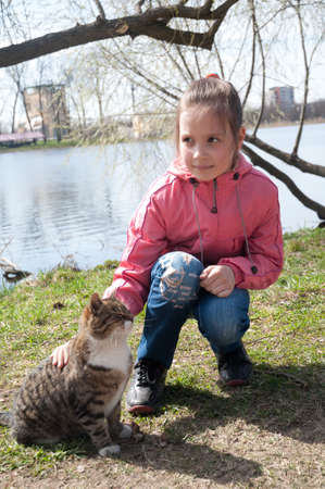 The little girl with a cat against lake photo