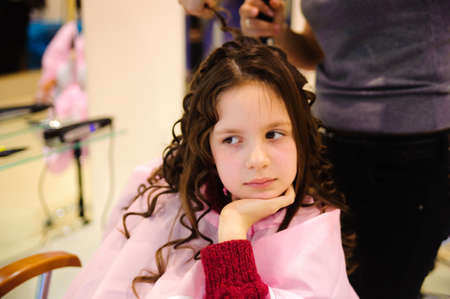 hairdress: The little girl doing a hairdress in a hairdressing salon