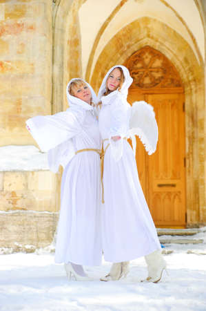 cassock: Two girls in suits of angels Stock Photo