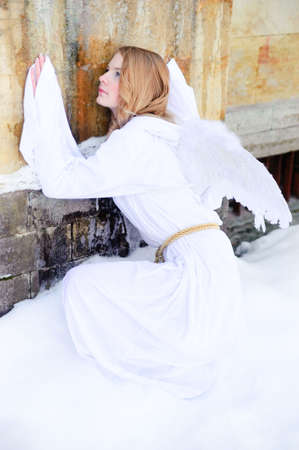 The young girl in a white attire with wings of an angel photo
