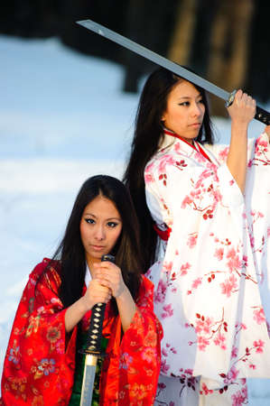 Beautiful brunette girls in a japanese kimono with a katana photo