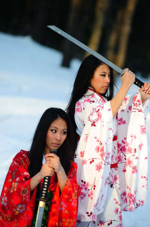 traditional weapon: Beautiful brunette girls in a japanese kimono with a katana Stock Photo