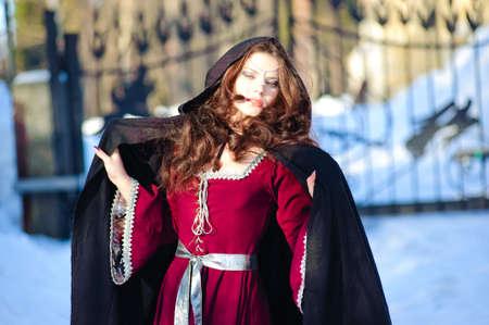 middeleeuwse jurk: Het meisje in een middeleeuwse jurk en een zwarte regenjas  Stockfoto