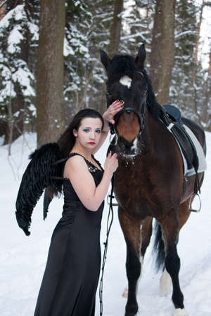 The girl in a black dress near to a horse photo
