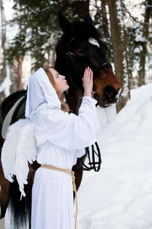 La niña en un traje de un ángel cerca a un caballo  Foto de archivo - 6761874
