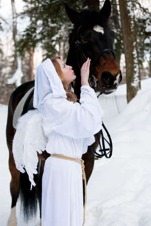 The girl in a suit of an angel near to a horse photo