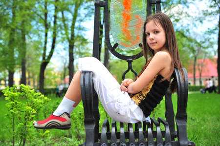 The little girl sitting on a pig-iron armchair in park Stock Photo - 7088402
