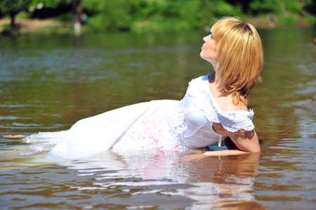 portrait of bride dressed in wedding gown in water photo