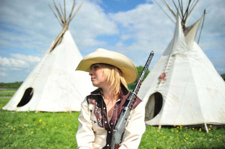 cree: The girl in a hat of the cowboy, sitting with a gun in hands against a wigwam