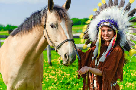 regalia: The girl in a suit of the American Indian near to a horse