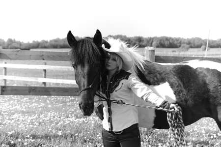 The girl the cowboy near to a horse photo