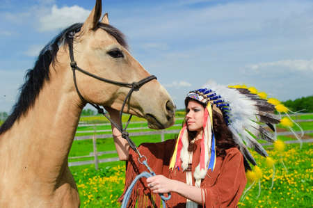 powow: The girl in a suit of the American Indian near to a horse