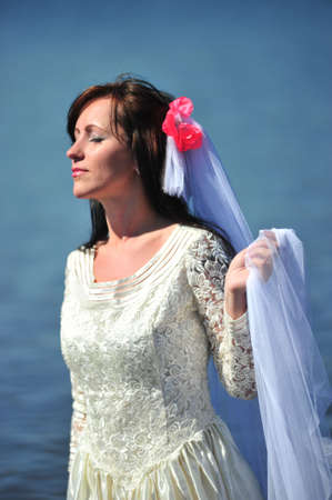 Portrait of the bride with a veil against lake photo