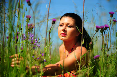 Young girl lying in grass and holding bunch of field flowers photo