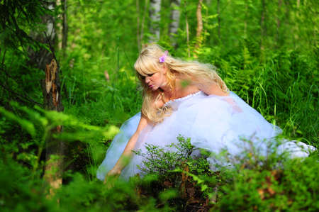The fair-haired bride in wood on a clearing photo