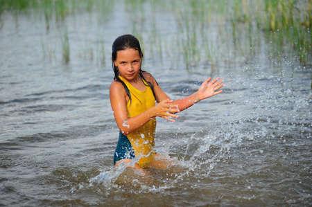 La pequeña niña salpicando con agua en el lago