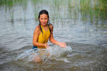 kiddies: The little girl splashing with water in lake